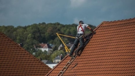 Roofer climbing a ladder on a roof